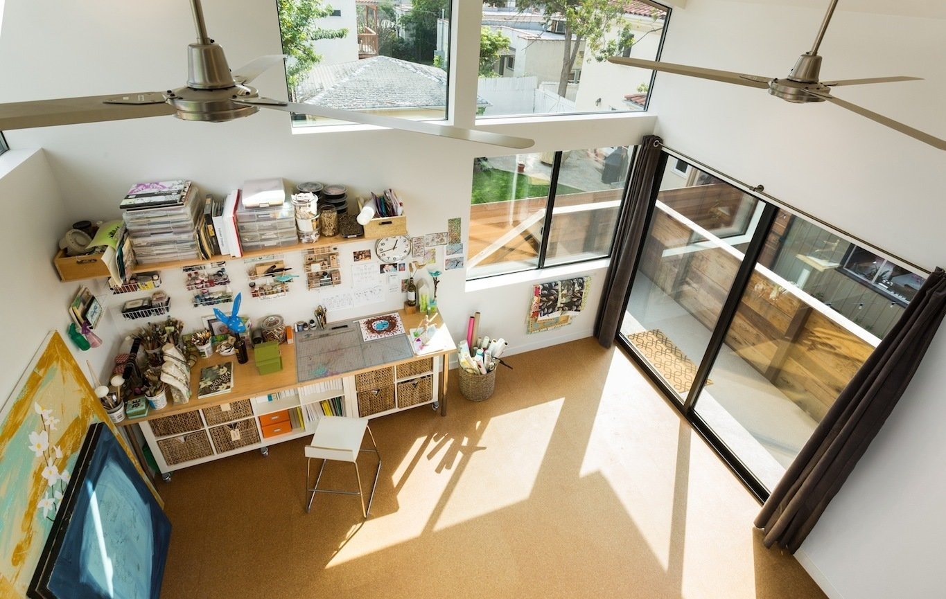 View from the book loft mezzanine.  Floors are cork tile Tagged: Craft Room, Bookcase, Storage, Desk, Shelves, Chair, Cork Floor, Track Lighting, Sliding Window Type, Doors, Metal, Picture Window Type, Exterior, and Sliding Door Type.  Mar Vista Art Studio by Hsu McCullough