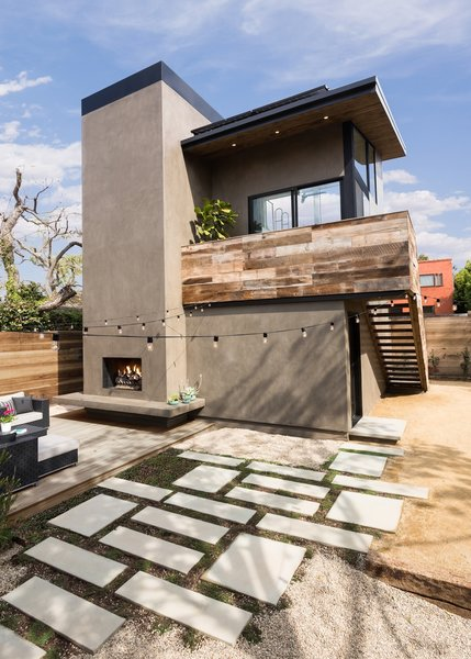 Modern home with desert, trees, walkways, hardscapes, back yard, concrete patio, porch, deck, wood patio, porch, deck, pavers patio, porch, deck, small patio, porch, deck, decking patio, porch, deck, horizontal fence, decomposed granite patio, porch, deck, wood fence, hanging lighting, exterior, metal, sliding door type, picture window type, sliding window type, and living room. View from the existing main house of the hardscape leading to the art studio and deck.  The exterior stair has open risers Photo 8 of Mar Vista Art Studio