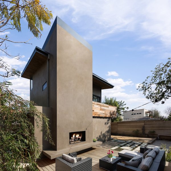 Modern home with sofa, coffee tables, light hardwood floor, chair, standard layout fireplace, gas burning fireplace, back yard, side yard, desert, hardscapes, trees, walkways, concrete patio, porch, deck, small patio, porch, deck, decking patio, porch, deck, wood patio, porch, deck, decomposed granite patio, porch, deck, pavers patio, porch, deck, horizontal fence, and hanging lighting. View of the raised deck, outdoor living room and fireplace at the art studio Photo 9 of Mar Vista Art Studio