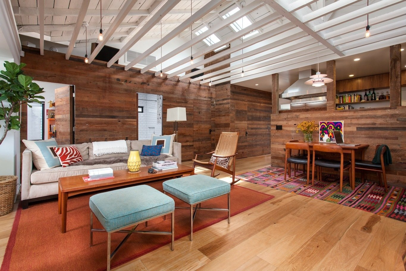 Living Room looking East towards bedrooms and bathroom hidden behind reclaimed wood siding clad walls Tagged: Chair, Sofa, Coffee Tables, Bench, Light Hardwood Floor, Ottomans, Pendant Lighting, Doors, Swing Door Type, Wood, and Interior.  Ashland Residence by Hsu McCullough
