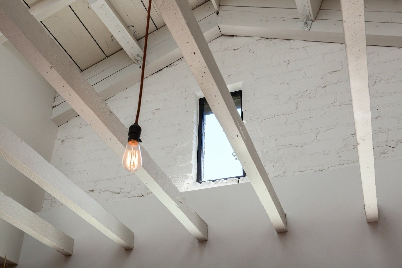 Detail of open ceiling framing, pendant light and window (former attic vent) within existing painted brick wall