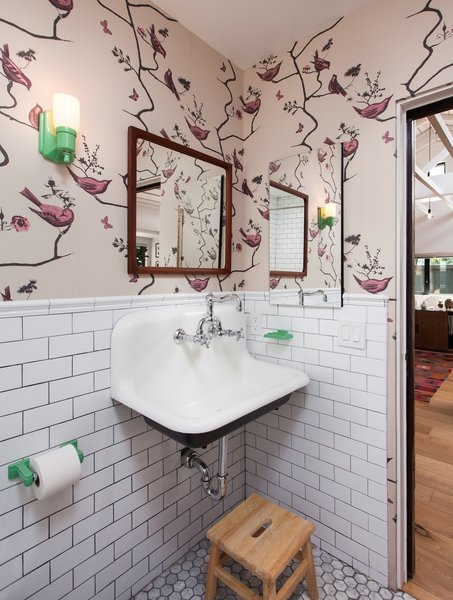 Modern home with marble floor, wall mount sink, subway tile wall, and bath room. Kid's Bathroom with playful wallpaper, subway tile and colorful bathroom accessories Photo 7 of Ashland Residence