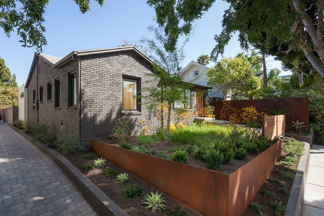 Front yard entry at driveway apron with corten landscape walls and gate beyond