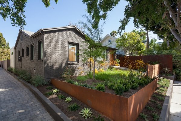Modern home with outdoor, front yard, garden, side yard, trees, grass, hardscapes, gardens, raised planters, walkways, wood fence, pavers patio, porch, deck, horizontal fence, and metal fence. Front yard entry at driveway apron with corten landscape walls and gate beyond Photo 9 of Ashland Residence