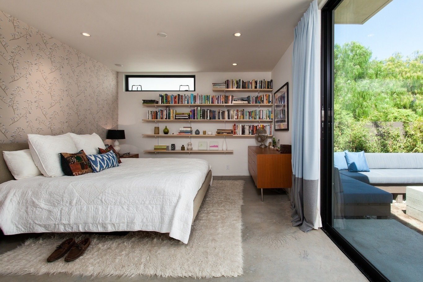 Bedroom at rear yard opens to patio Tagged: Bed, Bookcase, Dresser, Storage, Night Stands, Shelves, Recessed Lighting, Concrete Floor, Awning Window Type, Metal, Doors, Sliding Door Type, and Exterior.  Ashland Residence by Hsu McCullough