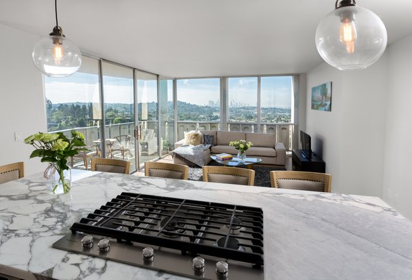 Modern home with sofa, coffee tables, chair, console tables, medium hardwood floor, pendant lighting, metal, windows, exterior, sliding door type, and picture window type. View of the city from the kitchen island  Photo 7 of LFT Residence
