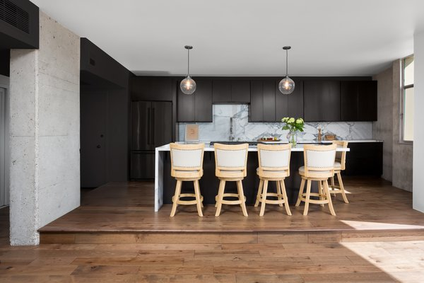 Modern home with kitchen, wood cabinet, marble counter, medium hardwood floor, marble backsplashe, refrigerator, cooktops, undermount sink, and pendant lighting. Kitchen with island bar seating and exposed concrete walls. Photo 5 of LFT Residence