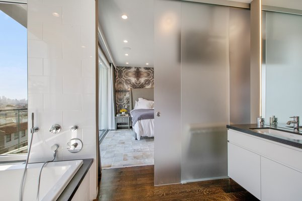 Modern home with bath room, granite counter, drop in tub, medium hardwood floor, ceiling lighting, and undermount sink. Photo 7 of LEED Platinum House in SF