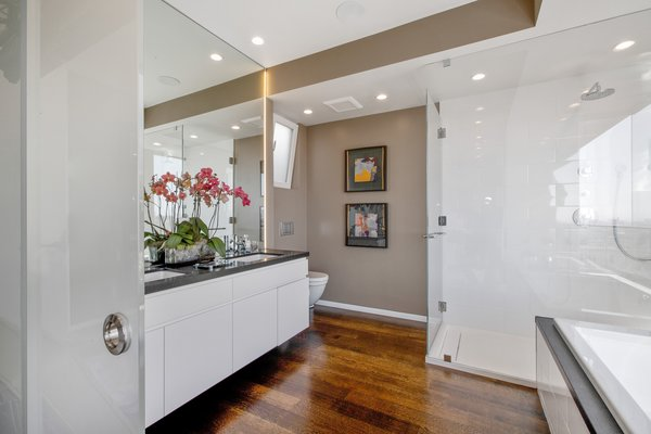 Modern home with bath room, granite counter, undermount sink, medium hardwood floor, enclosed shower, full shower, drop in tub, ceiling lighting, and one piece toilet. Photo 4 of LEED Platinum House in SF
