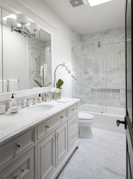 Modern home with bath room, marble counter, porcelain tile floor, undermount sink, drop in tub, enclosed shower, recessed lighting, wall lighting, stone tile wall, and one piece toilet. Guest Bath Photo 20 of Rustic elegance