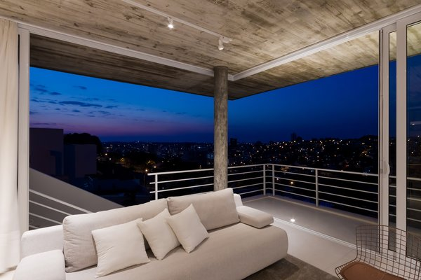 Modern home with living room, ceiling lighting, floor lighting, concrete floor, sofa, and corner fireplace. Photo 2 of View House