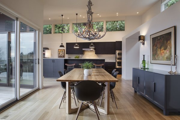 Modern home with dining room, chair, table, stools, bar, pendant lighting, ceiling lighting, and medium hardwood floor. Dining Room Photo 3 of West Hills Remodel