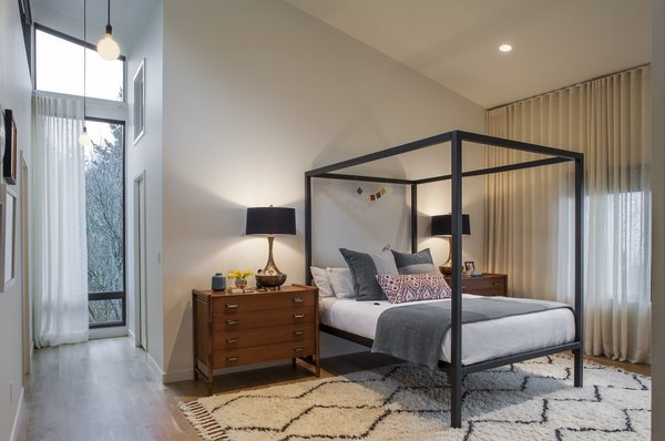 Modern home with bedroom, bed, night stands, ceiling lighting, and medium hardwood floor. Bedroom Photo 5 of West Hills Remodel
