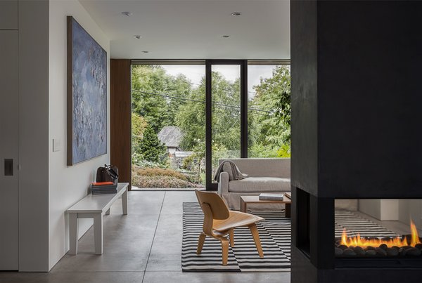 Modern home with living room, concrete floor, and two-sided fireplace. Helen Street by mw|works Photo 17 of Helen Street