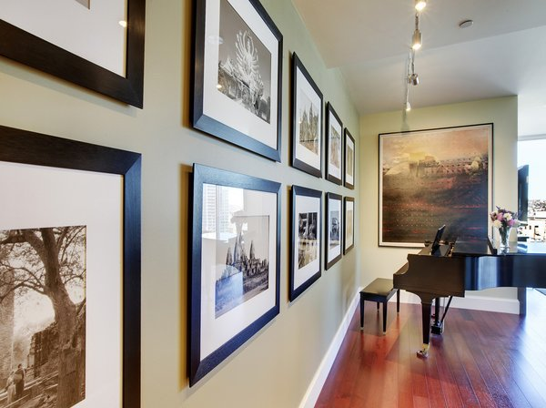 Modern home with hallway and medium hardwood floor. John is an avid world traveler and photographer. He took these photos (left) on one of his journeys to Thailand. We had them framed and hung in this bold arrangement. The Galen Garwood painting at the end of the hall was from their previous home. Originally, its frame was painted a light mauve, reminiscent of the 80s, so we chose to re-paint the frame an espresso/black. The small change brought the whole piece up-to-date. Photo 14 of Downsize Upstyle