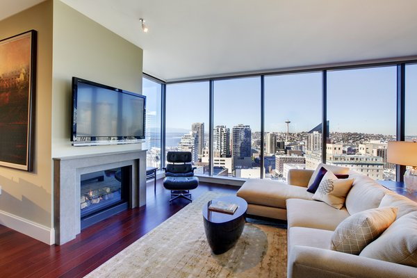 The living area showcases an amazing view of Puget Sound and downtown Seattle. Sectional from Patricia Edwards upholstered in AST fabric; cocktail table from Wendell Castle and the couples' original Eames Lounger.