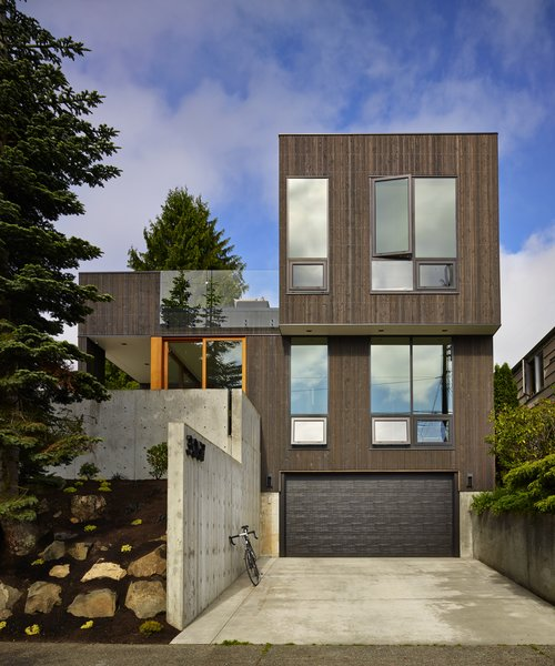 Modern home with rooftop, front yard, attached garage, casement window type, exterior, outdoor, boulders, trees, hardscapes, and concrete patio, porch, deck. Photo  of BLK_LAB
