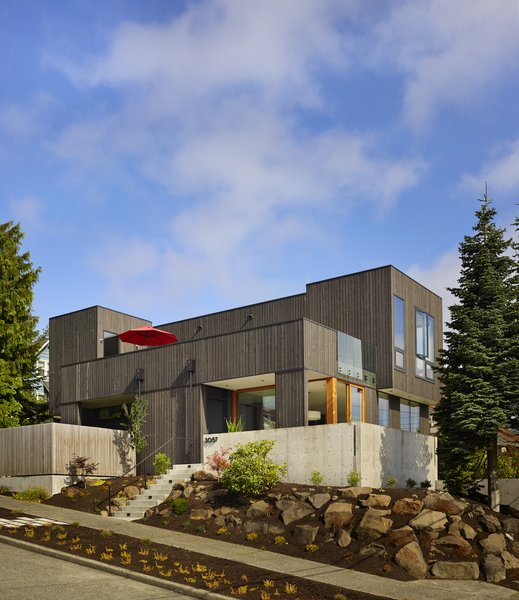 Modern home with front yard, side yard, trees, garden, slope, boulders, raised planters, concrete patio, porch, deck, casement window type, doors, and exterior. Photo 2 of BLK_LAB