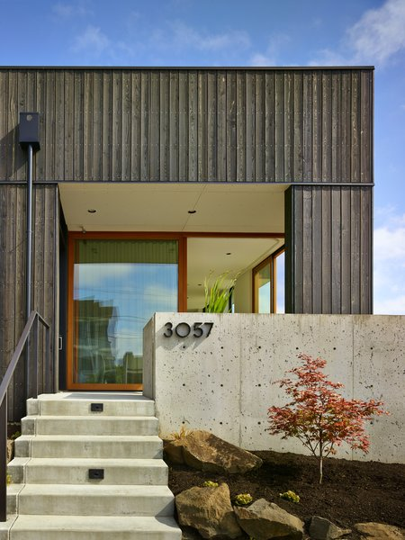 Modern home with front yard, slope, trees, boulders, hardscapes, concrete patio, porch, deck, side yard, doors, exterior, and sliding door type. Photo 3 of BLK_LAB