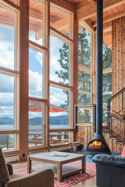 Modern home with light hardwood floor, wood burning fireplace, sofa, coffee tables, chair, windows, wood, metal, sliding window type, and picture window type. Photo 3 of Ferris Cabin