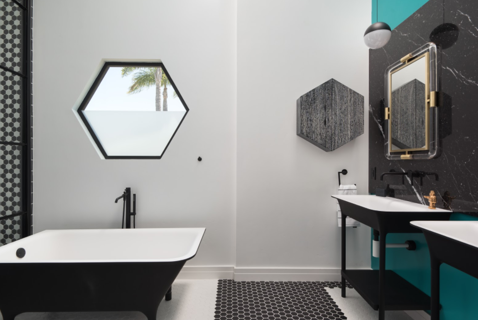 A Zucchetti Kos Italian imported tub serves as an anchor piece in the master bath.  Zucchetti vanities and fixtures along with creative color-block Hexagon pattern floor tiles, Flos String Lights designed by Michael Anastassiades, and a custom hex Fleetwood window present a clean and streamlined feel and the ultimate of bespoke design expression. Tagged: Bath Room, Ceramic Tile Floor, Pedestal Sink, and Freestanding Tub.  1980s Modern Meets The New Millennium by dasMOD