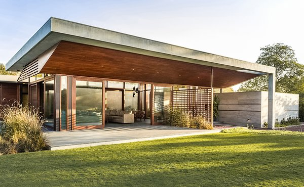 Modern home with outdoor, grass, trees, front yard, shrubs, hardscapes, and concrete patio, porch, deck. The front view of a retreat place. Photo  of The Open house