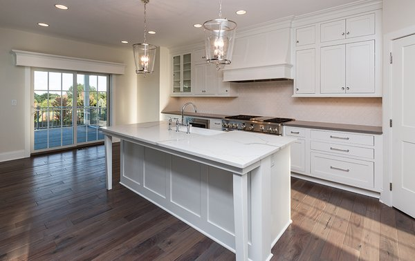 Modern home with kitchen, medium hardwood floor, and white cabinet. Photo  of Dynasty Partners Home