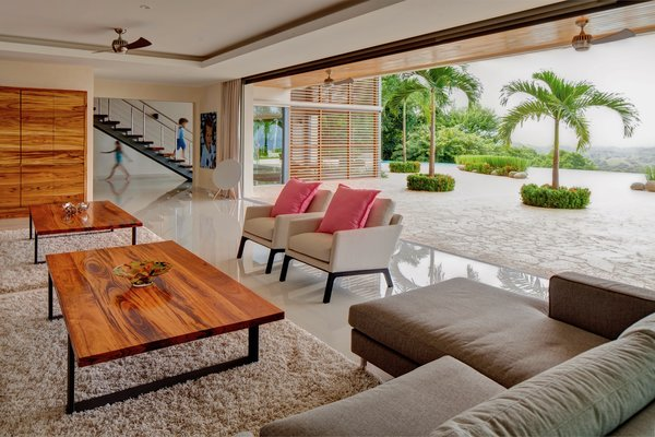 Modern home with living room, coffee tables, ceiling lighting, and porcelain tile floor. Living area flowing into outdoor terrace Photo 11 of Pacific Breeze house overlooking the Ocean