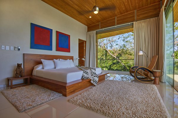 Modern home with bedroom, bed, ceiling lighting, and ceramic tile floor. Master bedroom Photo 12 of Pacific Breeze house overlooking the Ocean
