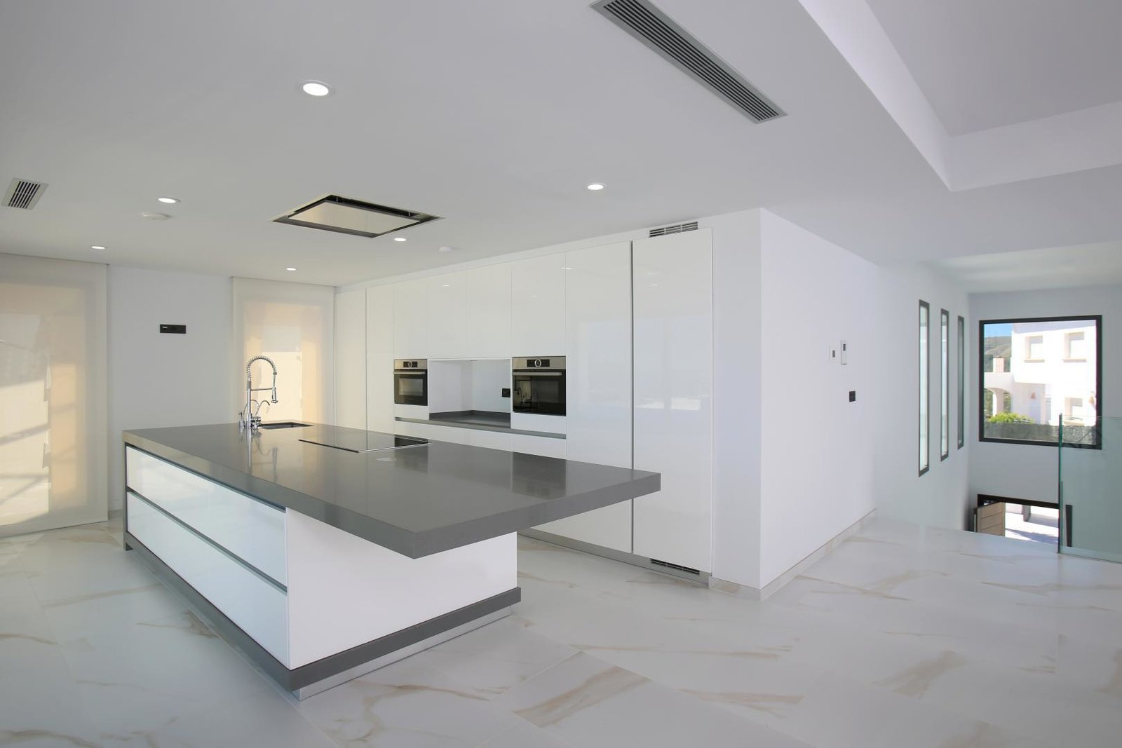 Kitchen Tagged: Kitchen, Engineered Quartz Counter, White Cabinet, Ceramic Tile Floor, Refrigerator, Wall Oven, Porcelain Tile Floor, Ceiling Lighting, Cooktops, Microwave, Range Hood, Dishwasher, Drop In Sink, and Undermount Sink.  Best Photos from Villa Demeter