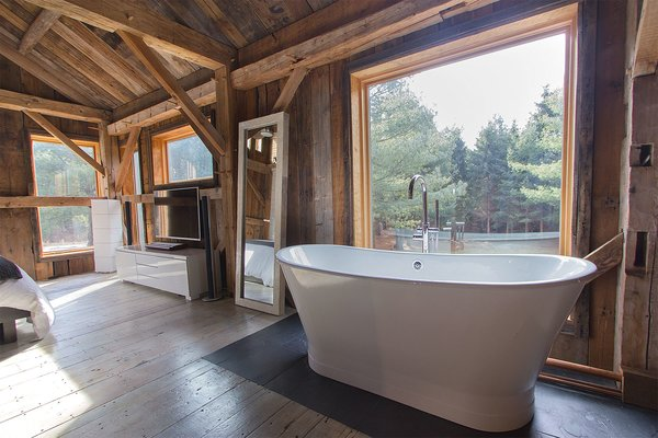 Modern home with bath room, light hardwood floor, one piece toilet, ceiling lighting, and freestanding tub. Photo 8 of Vintage Barn