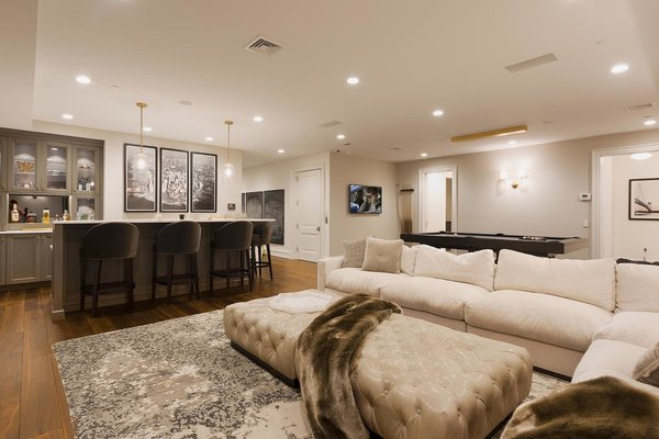 Modern home with living room, chair, sofa, sectional, ottomans, ceiling lighting, recessed lighting, and medium hardwood floor. Photo 2 of Bay Ridge Estate