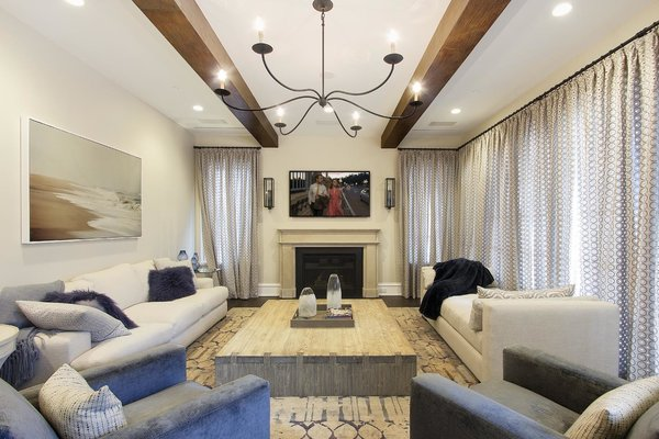 Modern home with living room, chair, sectional, recliner, sofa, ottomans, wall lighting, ceiling lighting, recessed lighting, coffee tables, medium hardwood floor, standard layout fireplace, wood burning fireplace, and gas burning fireplace. Photo 3 of Bay Ridge Estate