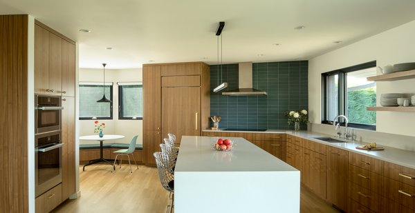 Expanded and updated kitchen with quarter sawn walnut cabinets, grey caesarstone counters and backsplash tile from the Modern line of Ann Sacks.