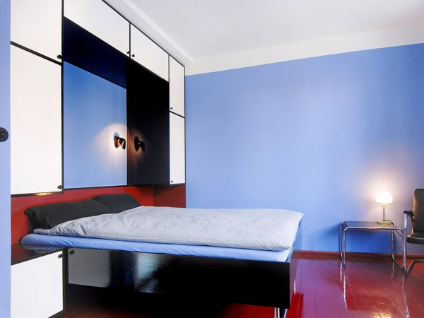 Modern home with bedroom, wardrobe, night stands, bed, chair, storage, ceiling lighting, table lighting, wall lighting, pendant lighting, accent lighting, and medium hardwood floor. master bedroom with large foldable bed, redesigned based on historic photographs Photo 10 of Taut´s Home (Tautes Heim) - Rentable museum of design and architecture of the 1920s