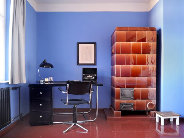 Modern home with office, study, lamps, chair, desk, and medium hardwood floor. writing desk with portrait of Bruno Taut and typical tiled stove Photo 11 of Taut´s Home (Tautes Heim) - Rentable museum of design and architecture of the 1920s