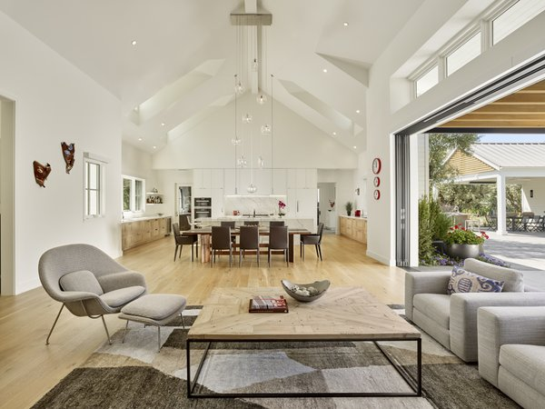 Modern home with kitchen, engineered quartz counter, stone slab backsplashe, pendant lighting, refrigerator, light hardwood floor, white cabinet, wall oven, cooktops, range, drop in sink, and wine cooler. Wood meet concrete.  Continuous living. Photo 2 of Wine Country Cool