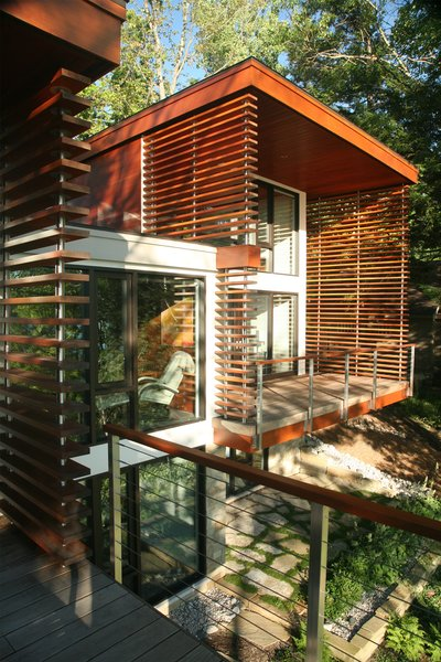 Modern home with outdoor, back yard, garden, trees, grass, hardscapes, gardens, shrubs, vegetables, flowers, boulders, wood patio, porch, deck, walkways, large patio, porch, deck, small patio, porch, deck, stone patio, porch, deck, decking patio, porch, deck, and landscape lighting. Photo 2 of Walloon Lake House