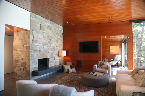 Modern home with living room, bench, chair, recliner, sofa, end tables, ottomans, coffee tables, console tables, ceiling lighting, table lighting, accent lighting, floor lighting, medium hardwood floor, limestone floor, slate floor, and standard layout fireplace. Photo 5 of Walloon Lake House