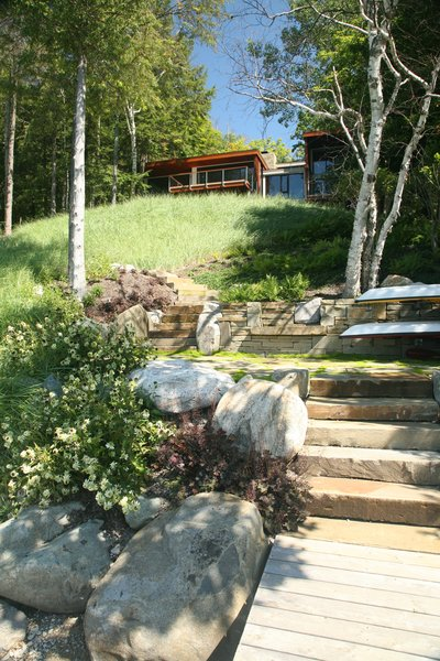 Modern home with outdoor, back yard, slope, field, woodland, garden, shrubs, trees, grass, walkways, gardens, hardscapes, wood patio, porch, deck, boulders, flowers, landscape lighting, large patio, porch, deck, small patio, porch, deck, pavers patio, porch, deck, and stone patio, porch, deck. Photo 8 of Walloon Lake House