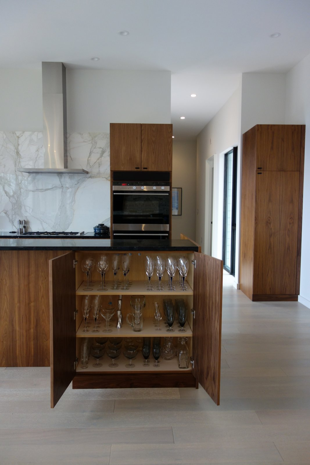 Tagged: Kitchen, Wood Cabinet, Marble Counter, Light Hardwood Floor, Granite Counter, Accent Lighting, Wall Oven, Range Hood, Ceiling Lighting, Stone Slab Backsplashe, Cooktops, and Range.  Long House HS by Matthew Dudzik