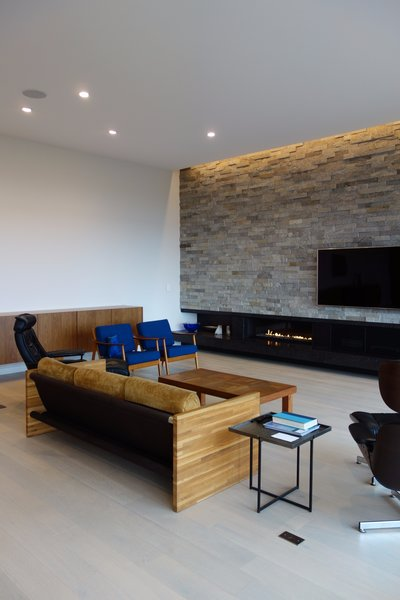 Modern home with living room, bench, chair, sofa, recliner, end tables, ottomans, coffee tables, ceiling lighting, console tables, wall lighting, recessed lighting, accent lighting, floor lighting, light hardwood floor, and ribbon fireplace. Photo 7 of Long House HS