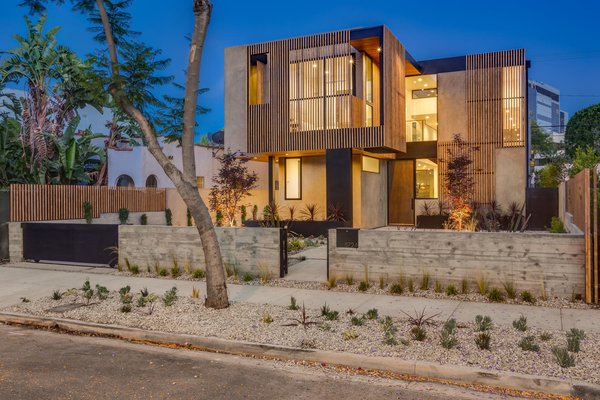Modern home with outdoor, trees, hardscapes, front yard, gardens, walkways, flowers, horizontal fence, raised planters, vertical fence, wood fence, and landscape lighting. Front Exterior, Night Photo  of The Rosewood Residence