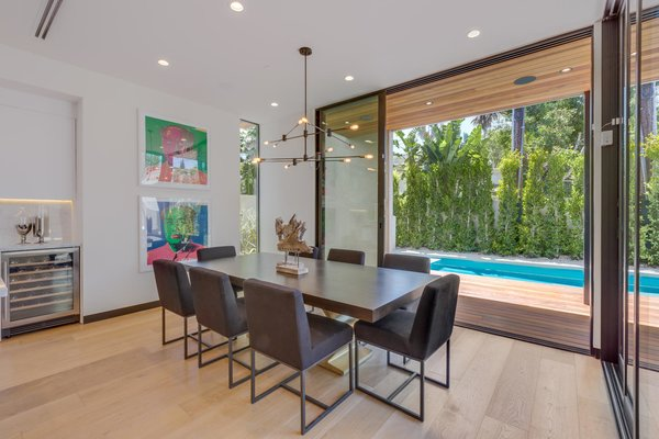 Modern home with dining room, chair, table, ceiling lighting, recessed lighting, pendant lighting, and light hardwood floor. Dining Photo 9 of The Rosewood Residence