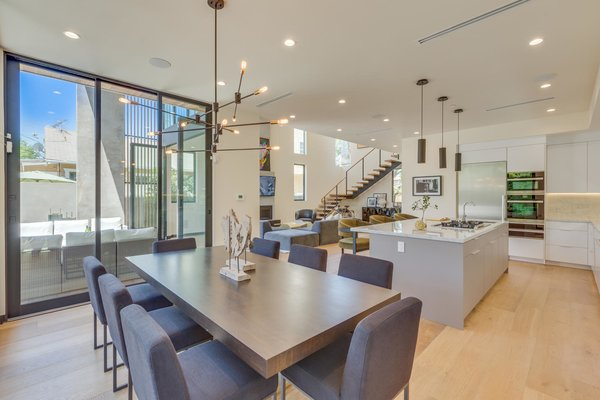Modern home with dining room, chair, ceiling lighting, table, track lighting, accent lighting, light hardwood floor, and pendant lighting. Dining/Kitchen Photo 8 of The Rosewood Residence