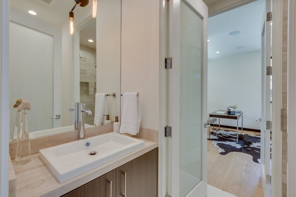 Modern home with bath room, marble counter, enclosed shower, drop in sink, ceiling lighting, recessed lighting, wall lighting, one piece toilet, and porcelain tile floor. Downstairs Bathroom Photo 11 of The Rosewood Residence