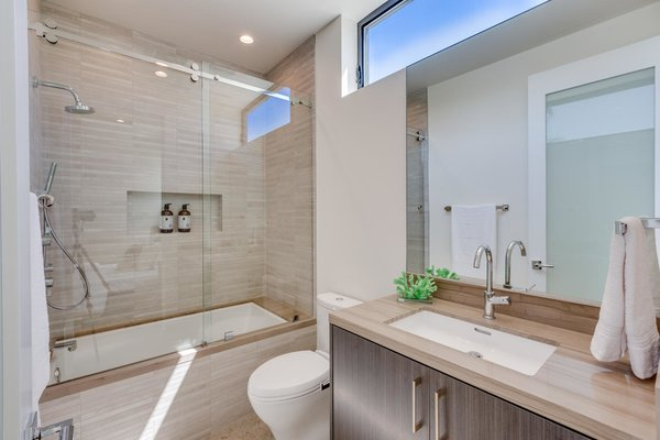 Modern home with bath room, drop in sink, soaking tub, marble counter, enclosed shower, ceiling lighting, stone tile wall, one piece toilet, and porcelain tile floor. Upstairs 2nd Bathroom Photo 17 of The Rosewood Residence