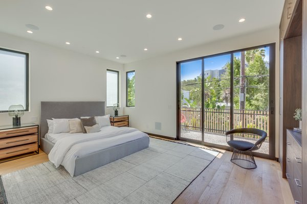 Modern home with bedroom, bed, storage, night stands, chair, ceiling lighting, table lighting, accent lighting, and light hardwood floor. Master Suite Photo 18 of The Rosewood Residence