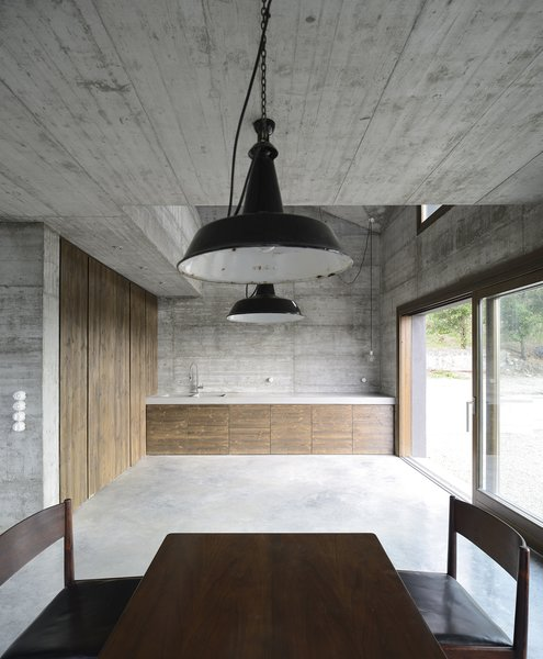 Modern home with kitchen, wood counter, concrete counter, concrete floor, table lighting, pendant lighting, ceiling lighting, and dishwasher. Photo 14 of HOUSE R
