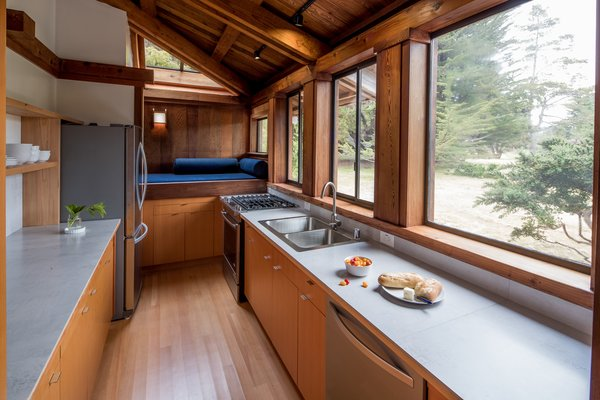 Modern home with kitchen, wood cabinet, light hardwood floor, track lighting, drop in sink, range, and concrete counter. Photo 2 of Hinoki House